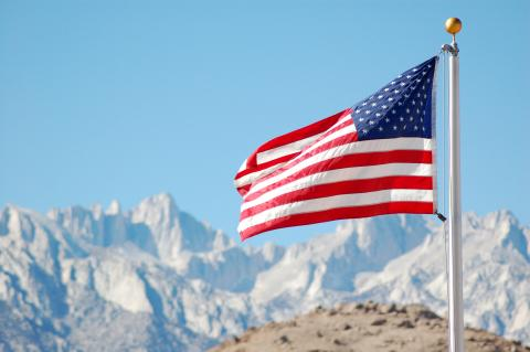 American flag flying in front of mountains