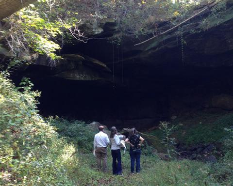 Photo of 3 people standing at the entrance of Little Hocking Cave