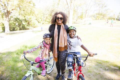A woman poses with two kids at Frogtown Park and Farm