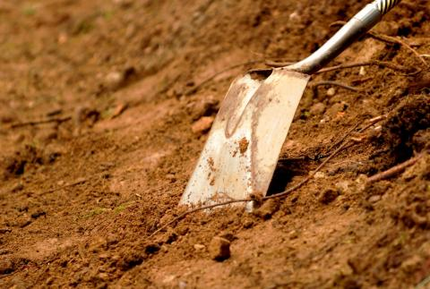 A close up of a shovel in dirt
