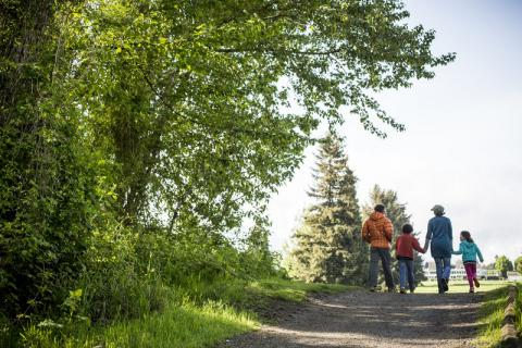 A family walks down a path at Colwood Park in Portland, Oregon
