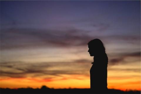 Woman silhouetted against a sunset