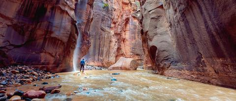 A man stands in a deep canyon by a waterfall