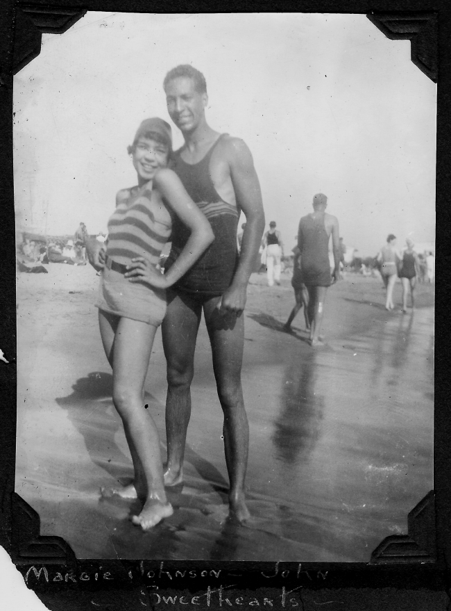 Sweethearts Margie Johnson and John Pettigrew at the crowded Pacific Ocean shoreline in 1927. This photograph and others at Bruce's Beach were featured under the title of this caption on a page in the scrapbook of LaVera White who lived in Los Angeles.