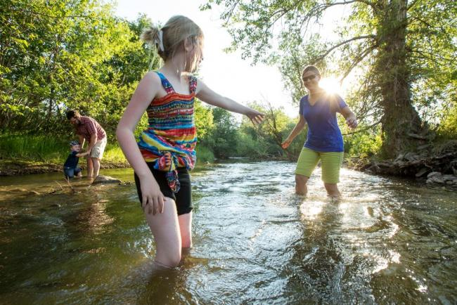A mom and two daughters play in a creek