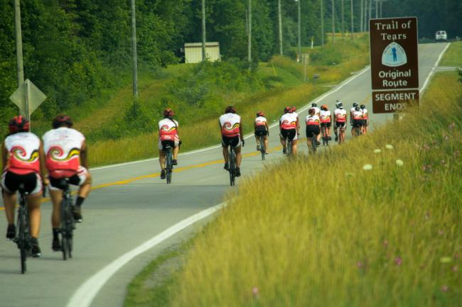 "Cyclists ride past a sign reading ""Trail of Tears Original Route"""