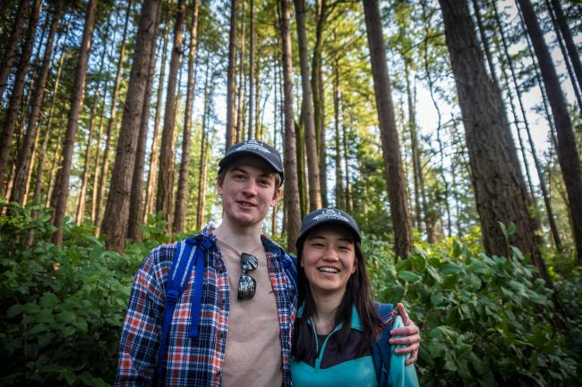 Two hikers in their 20s smile for a photo in a forest