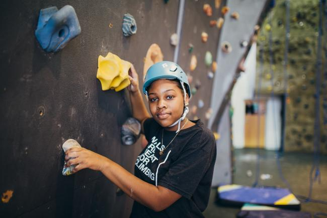 A middle school aged girl wearing a climbing helmet prepares to climb an indoor wall