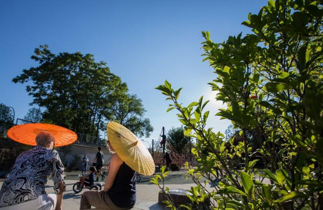 Two people sit under umbrellas in the sun