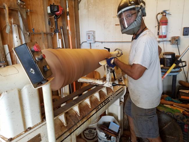 A man in a face mask at a lathe