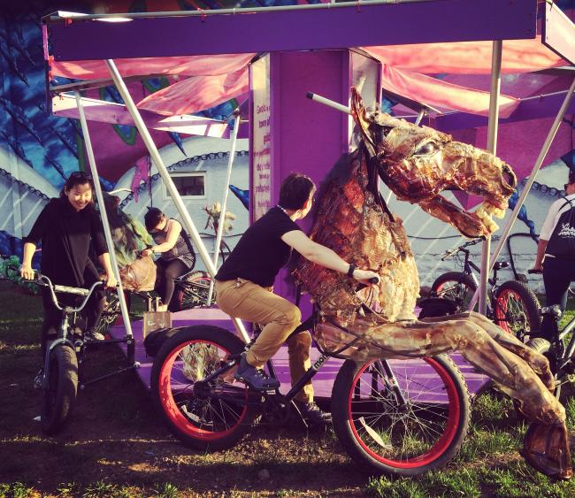 People ride a pedal-powered carousel
