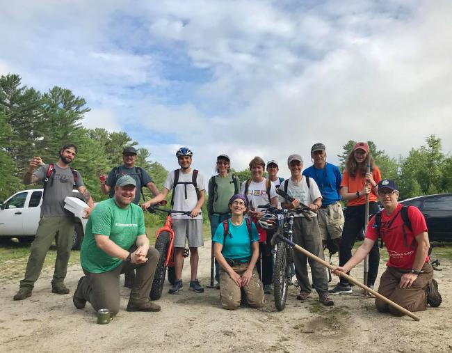 A trail crew poses for a photo with tools and bikes