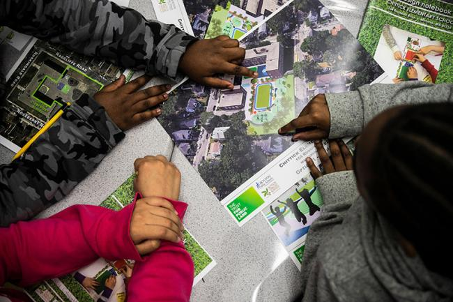 Photo of kids hands pointing to a map drawing of a playground and park