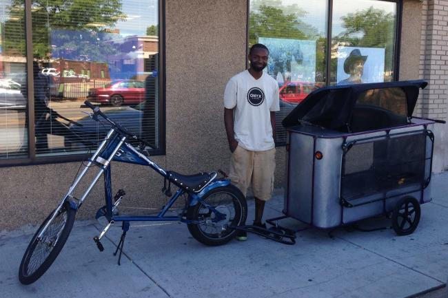 A man stands in front of a bicycle pulling a trailer