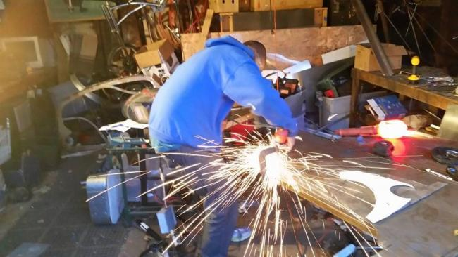 Brandon Brown welds a bike in his shop