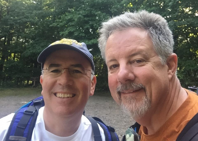 Two men smile for a selfie in a forest
