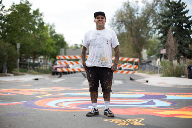 Santiago Jaramillo stands in front of a mural he helped design in Westwood