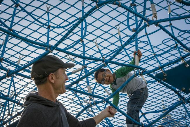 A boy in glasses climbs in a net
