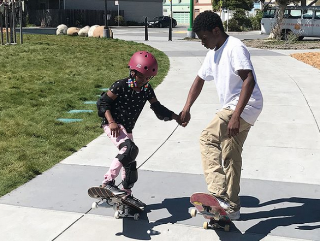 A boy helps a young girl learn how to skateboard