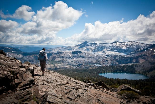 A hiker looks over a high mountain vista