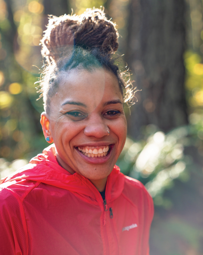 Faith Briggs smiles for a portrait in a forest
