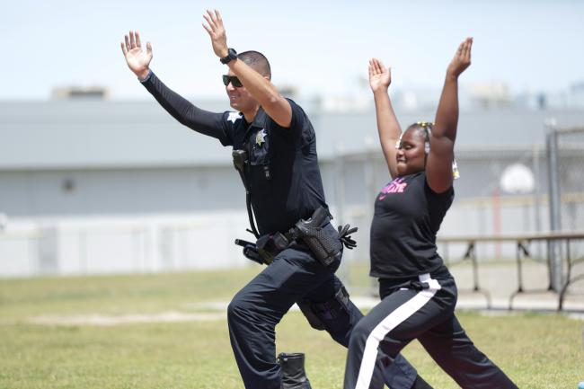 A policeman and a kid do yoga in a schoolyard