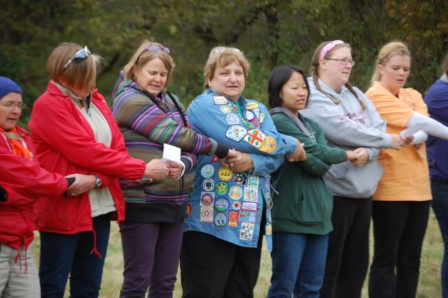 Former Girl Scouts hold hands around a campfire