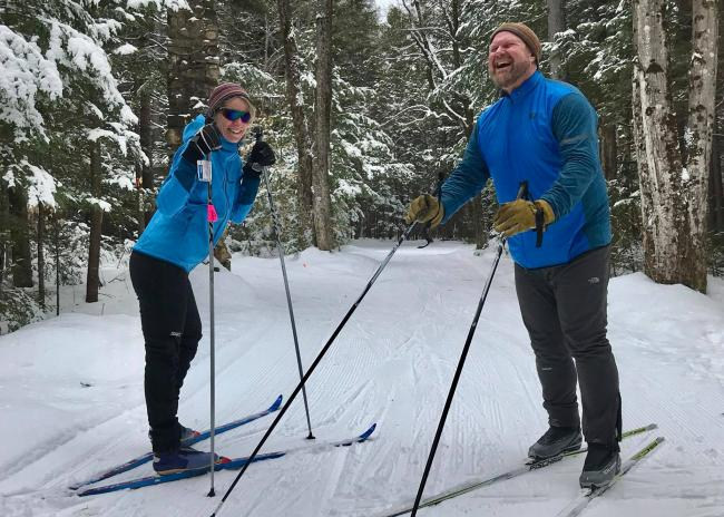 A man and a woman on cross country skis in a forest