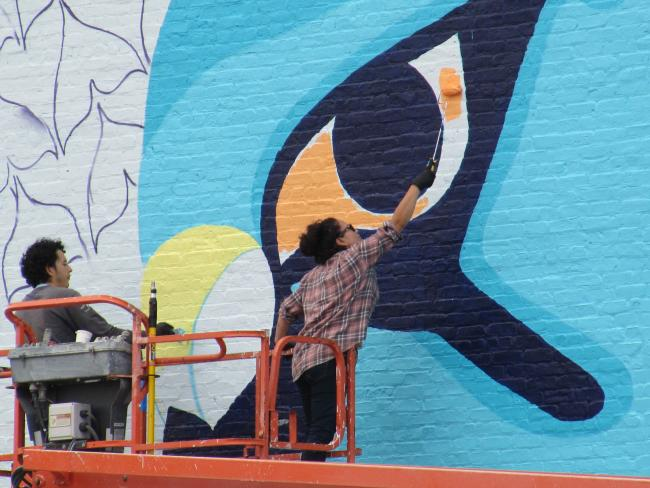A woman on a lift paints a giant falcon eye with a roller