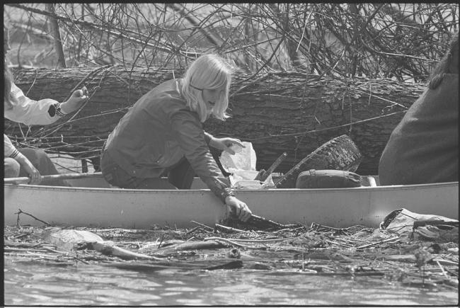 A girl in a canoe picking trash out of a river in 1970