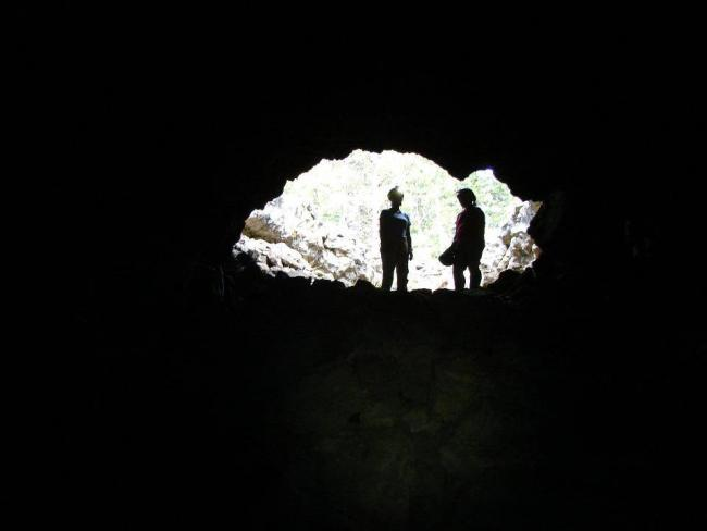 Two silhouetted figures in the mouth of a cave