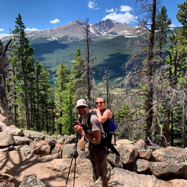 Trevor Hahn and Melanie Knecht smile for a photo on trail in front of a mountain vista. Trevor carries Melanie on his back.