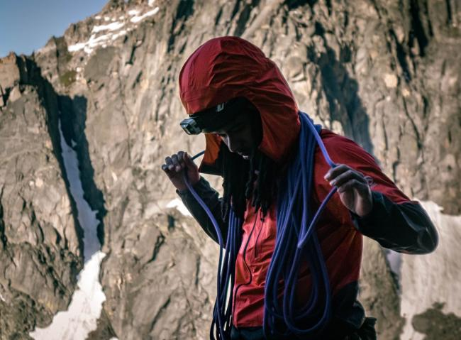 Manoah Ainuu wraps a climbing rope around his shoulders with a big mountain in the background