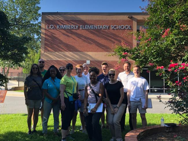 10 people smile for the camera in front of Kimberly Elementary School