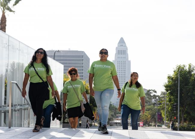 Five women in matching green t-shirts climb the stairs in front of Los Angeles City Hall.