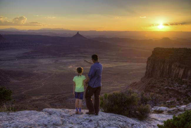 A father and daughter stand on an overlook at Indian Creek in Bears Ears National Monument at sunset