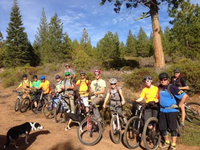 A group of people on mountain bikes poses for the camera