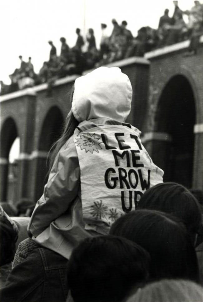 "A vintage photo from 1970 of a girl sitting on her parent's shoulders wearing a jacket reading ""Let me grow up"""