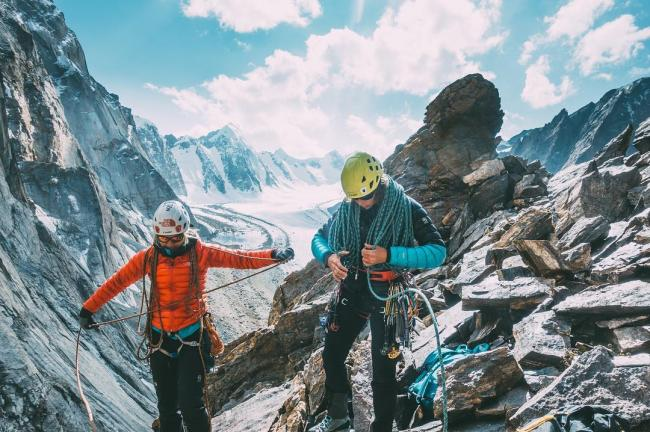 Two women climb above a glaciated valley