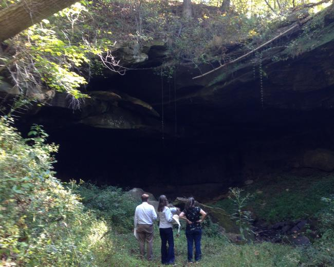 Three people stand at the mouth of a wooded cave