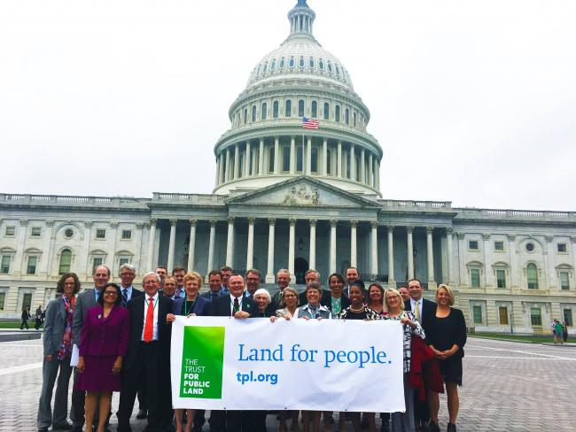 Trust for Public Land volunteers pose with a banner before the U.S. Capitol