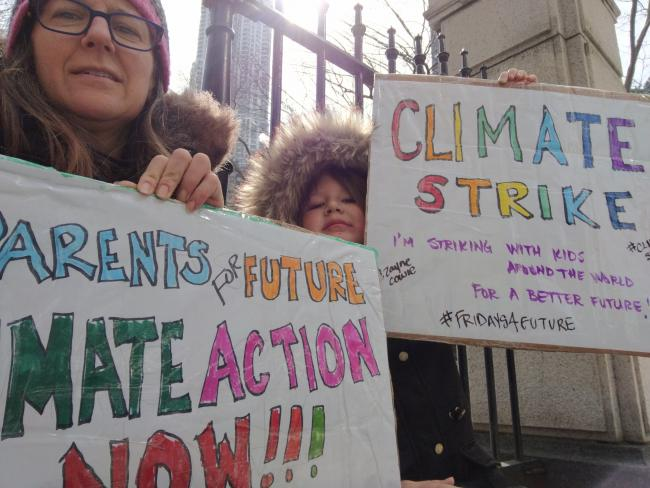 A mom and son hold climate strike signs wearing winter coats