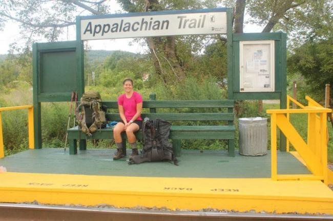 A woman with a backpack sits on the A.T. train stop bench