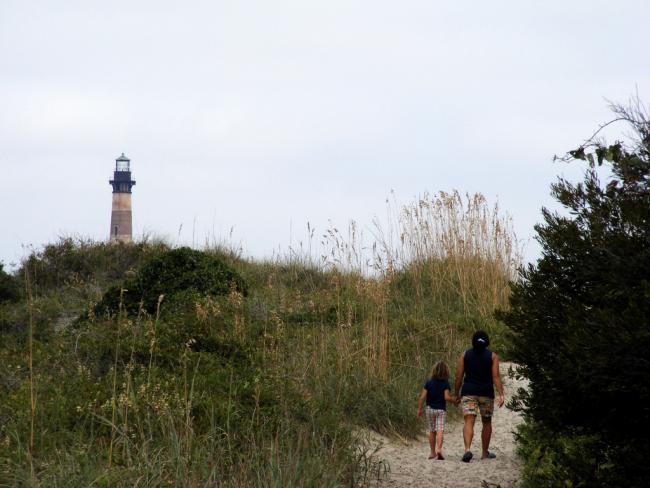 A mom and child walk toward the lighthouse on Morris Island