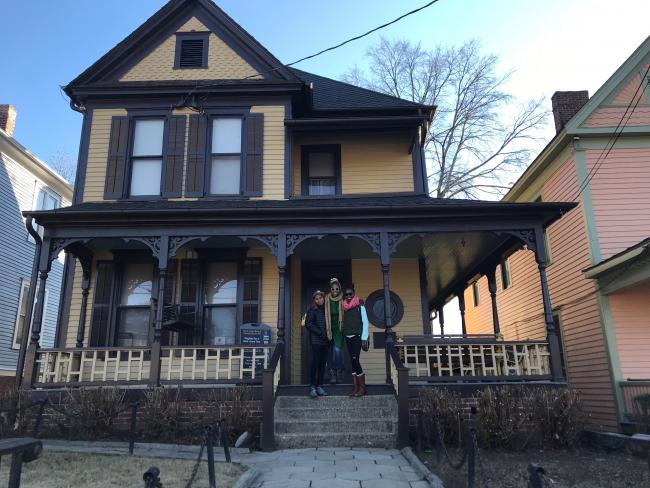 A woman and two teenagers on the porch of MLK's childhood home