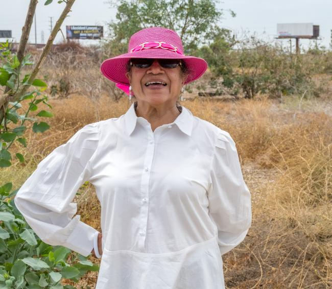 Rosa Rodriguez poses for the camera at the site of the future Urban Orchard in South Gate, California