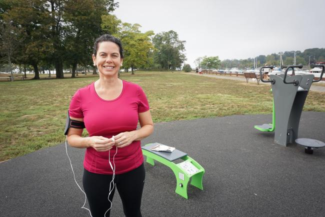 A woman in workout garb at an outdoor exercise area