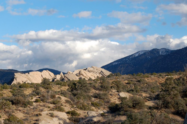 Desert rock formations and snowy mountains in the background