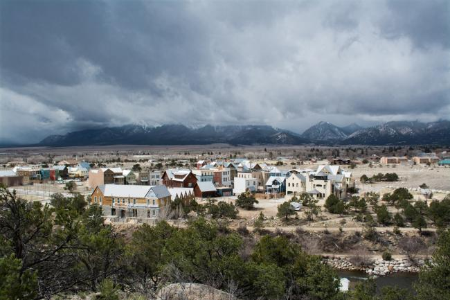 A small town in a mountain valley under cloudy skies