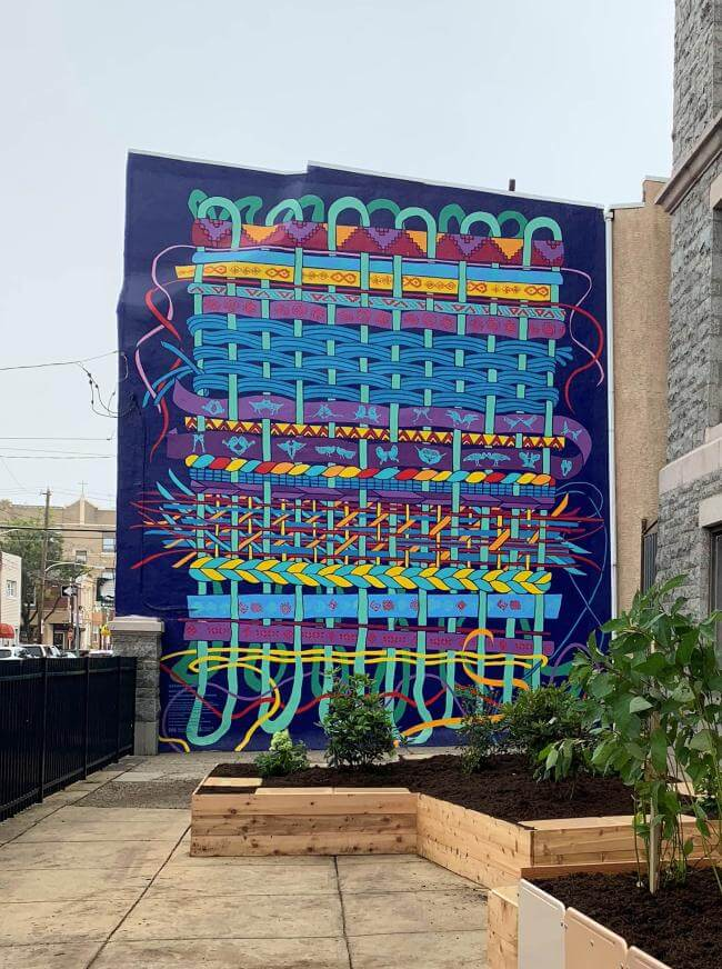 A two-story tall mural in an array of colors represents the theme of weaving.